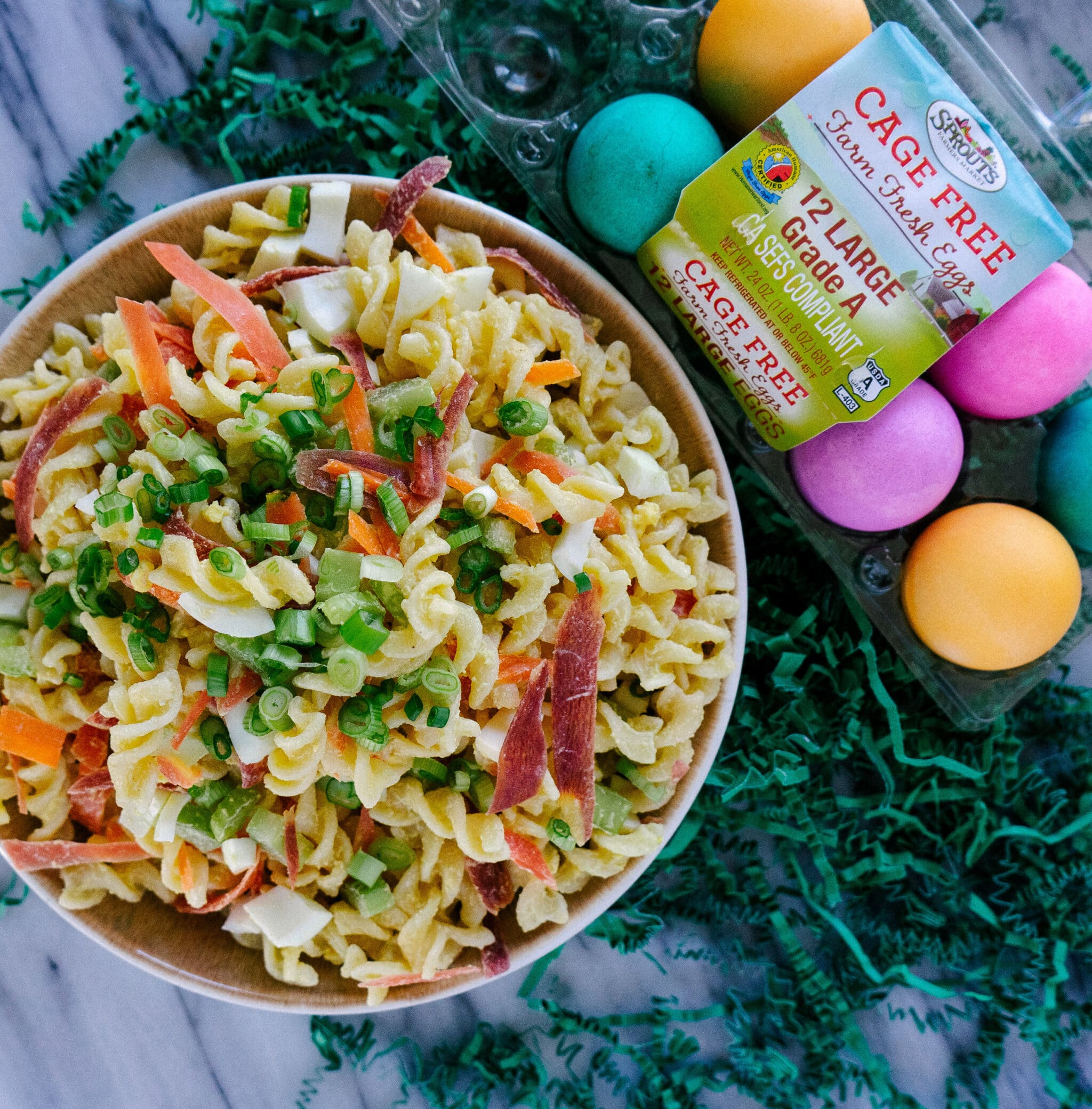 Above view of deviled egg pasta salad in a bowl with dyed Easter eggs on the side