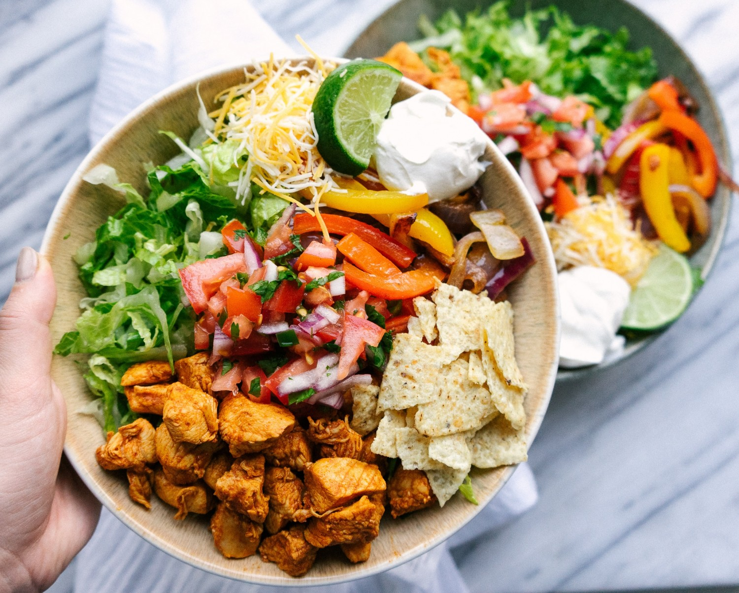 Above view of chicken fajita salad in a serving bowl with lots of toppings