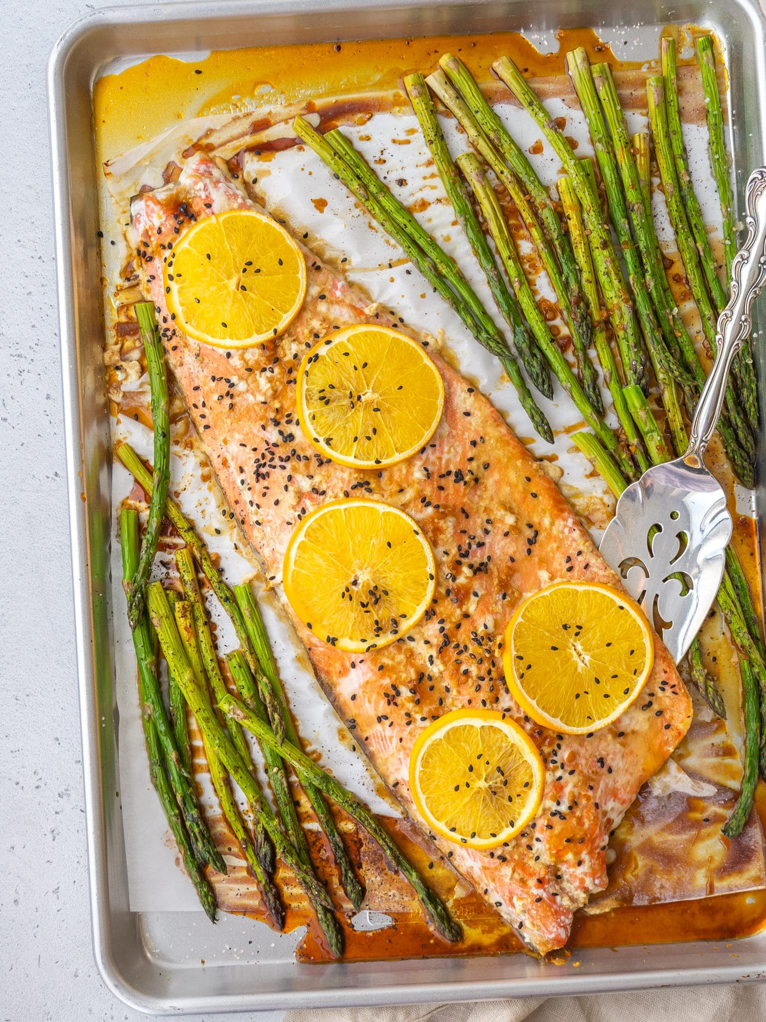 Above view of orange glazed salmon on a baking sheet with asparagus