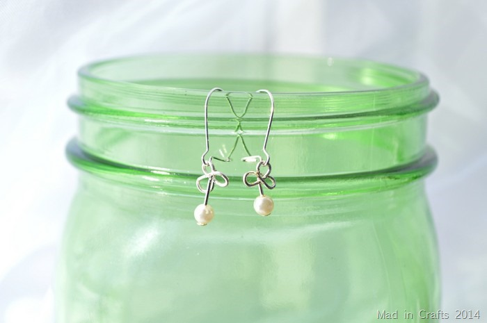 wire and pearl shamrock earrings hanging on a green mason jar