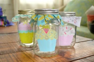 cupcakes painted on mason jars on a wood table