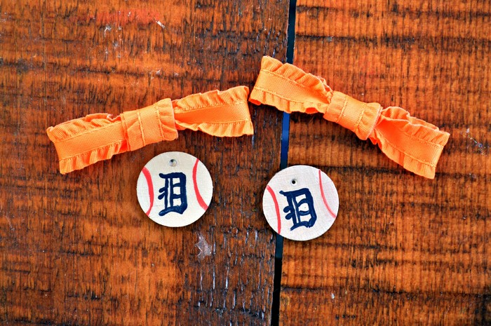 orange bows and painted wood baseballs on a wood table