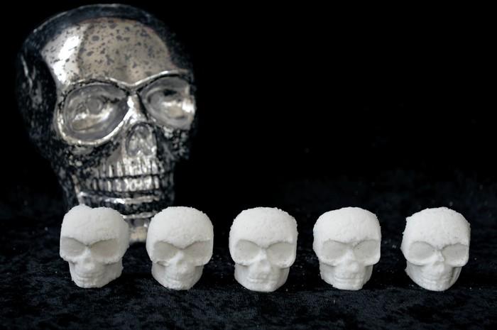 white skull shaped bath bombs on a black background
