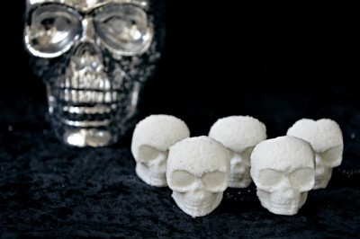 white skull shaped bath bombs on a black background