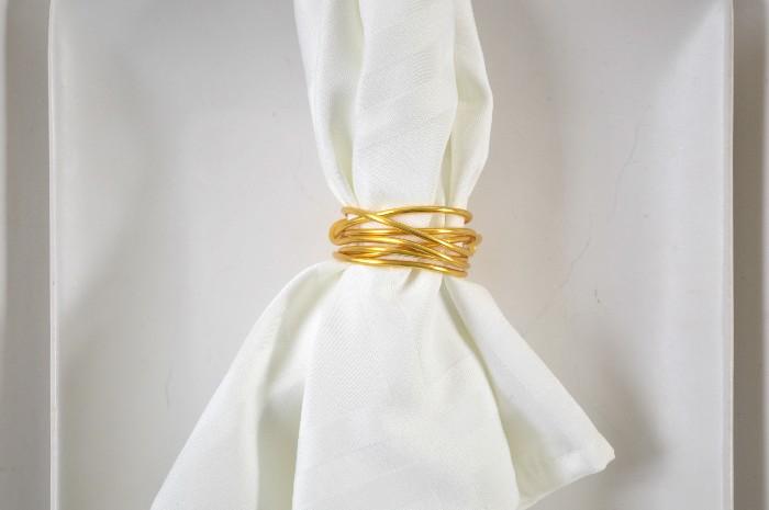 closeup of a wire napkin ring on a white napkin