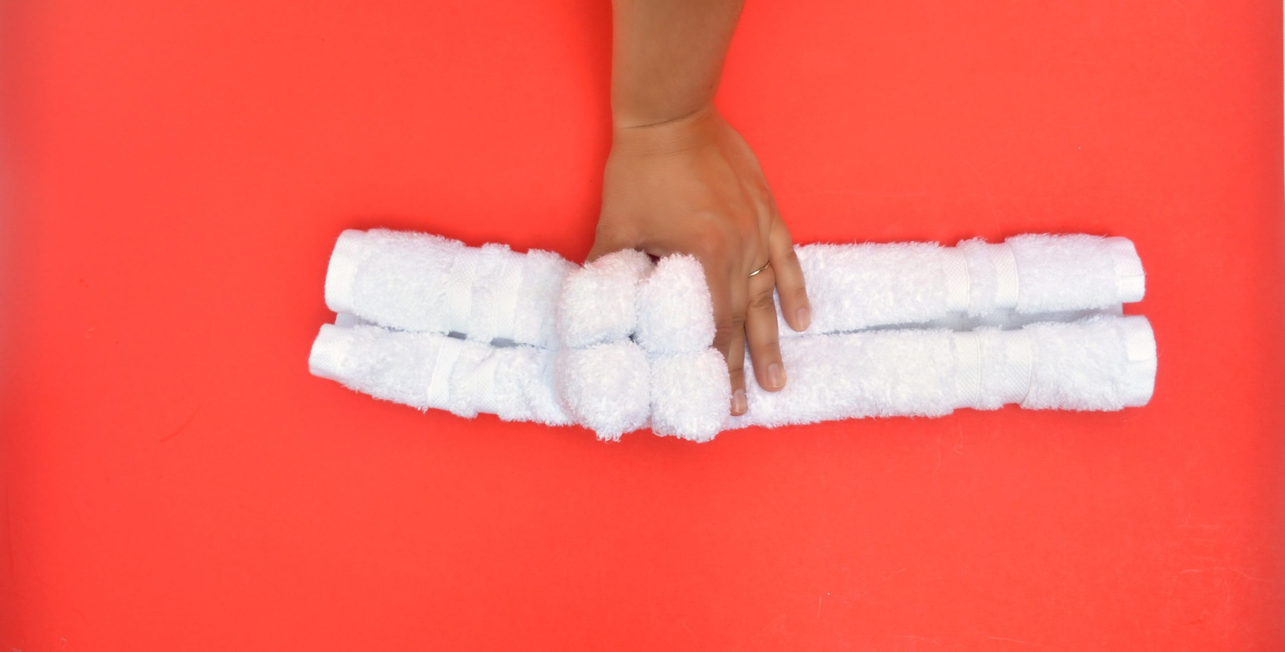 hand folding a towel on a red background