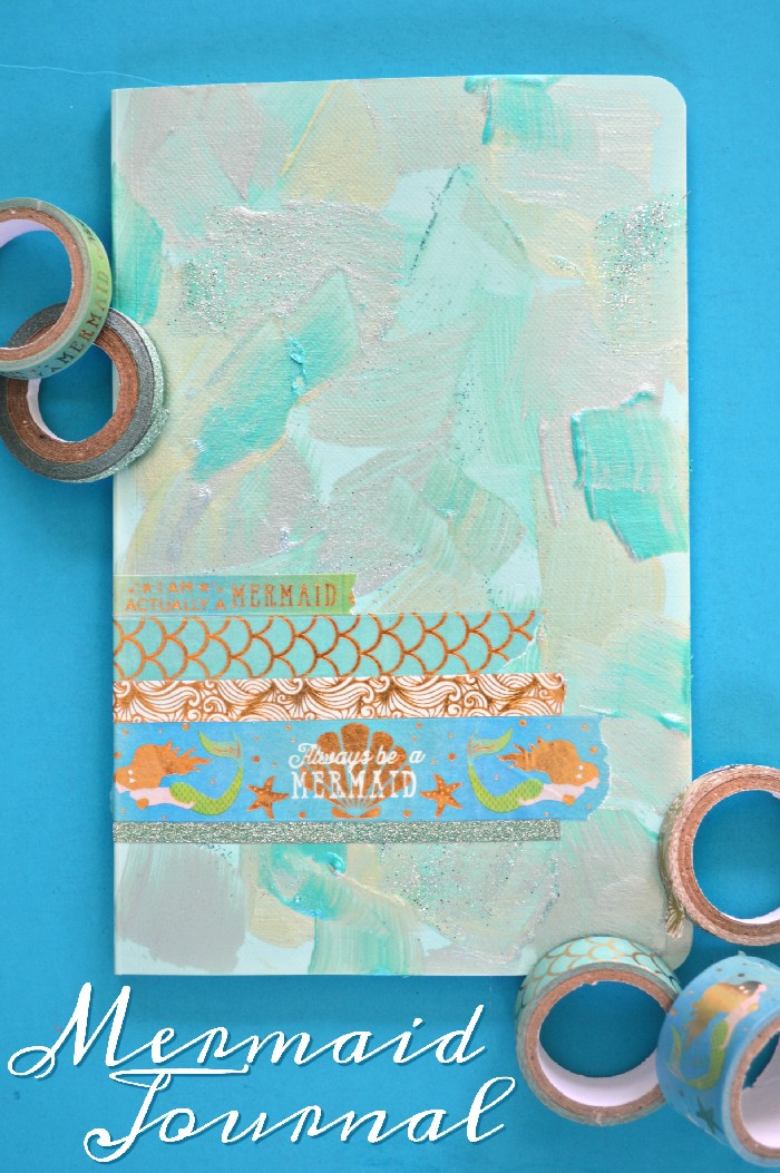 painted notebook with mermaid washi tape on a blue background