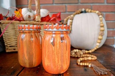 orange and yellow drip painted mason jars next to white pumpkins