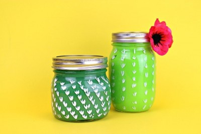 2 cactus painted mason jars on a yellow background