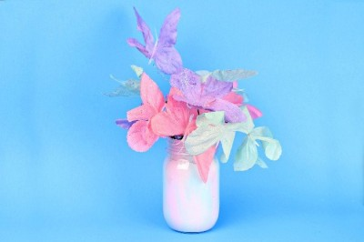 pastel painted mason jar filled with pastel flowers on a blue background