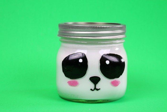Panda painted mason jar on a green background