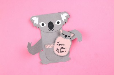 Cricut cut koala and baby card on a pink background