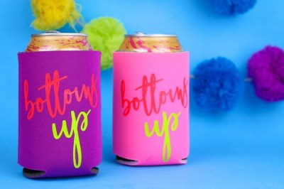 neon can koozies that say Bottoms Up in vinyl in front of a blue background