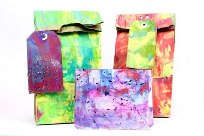 colorfully painted gift bags, tags, and cards on a white background