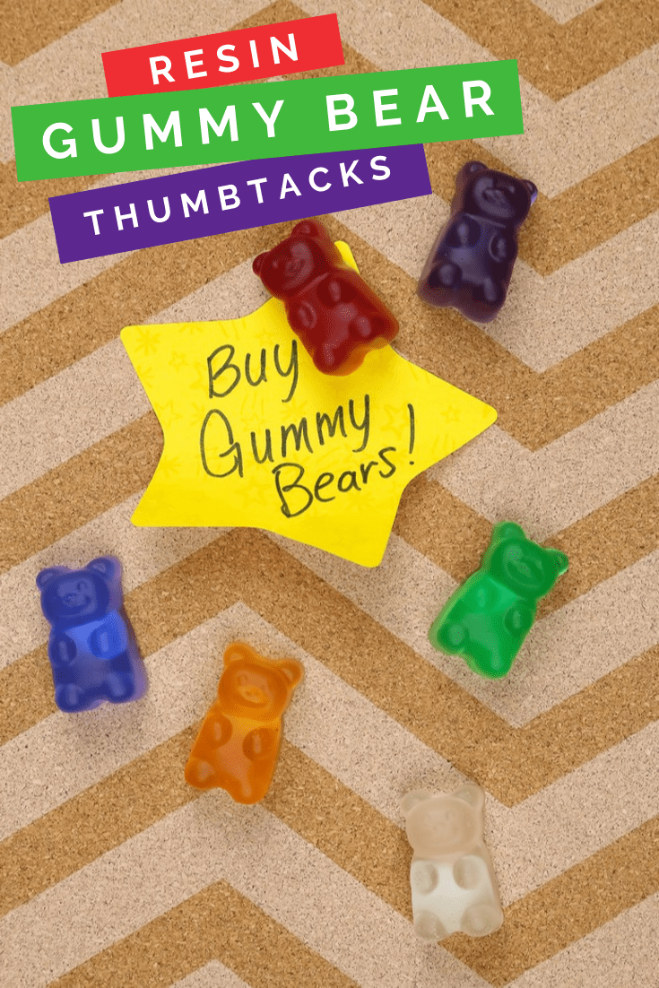 colorful resin gummy bear thumbtacks on a cork board