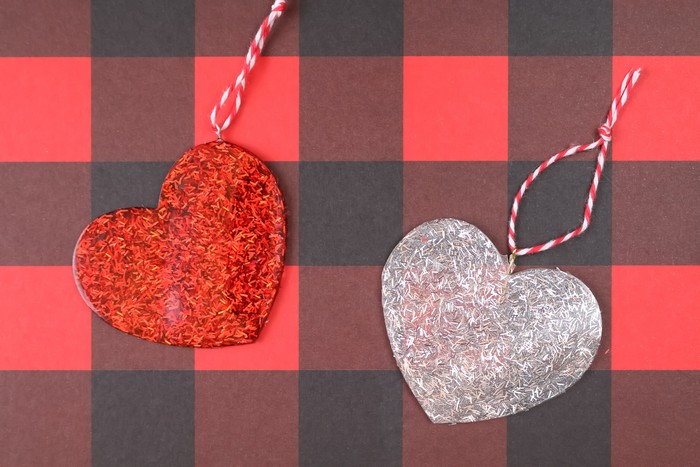 glitter resin heart ornaments on a plaid background