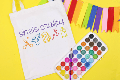 she's crafty svg design on a tote bag, watercolor palette, and rainbow bunting on a yellow background