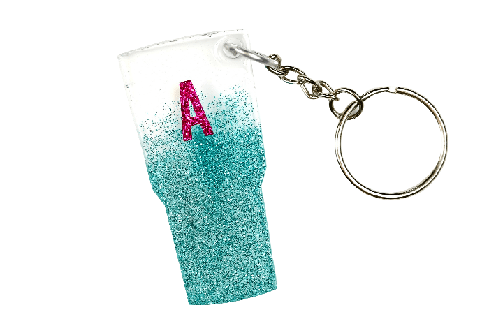 close up of a glitter tumbler key chain with a pink A