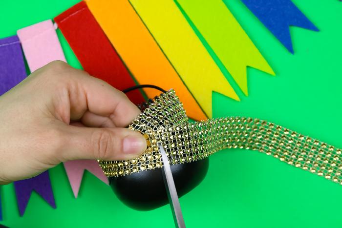 hands cutting rhinestone ribbon to fit a mini pot of gold