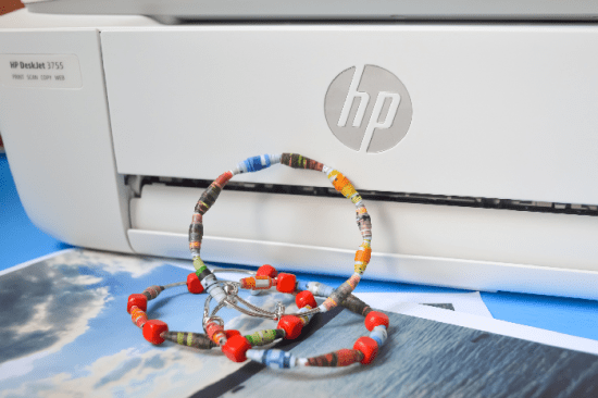 rolled paper beads on bracelets leaned against a printer