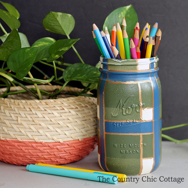 green and blue plaid painted mason jar next to a plant