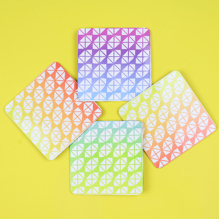 Colorful Infusible Ink coasters on a yellow background