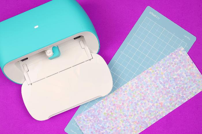 Cricut Joy, Cricut mat, and patterned paper on a purple background