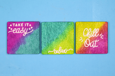 Colorful dyed wood coasters with white vinyl sayings on a blue background