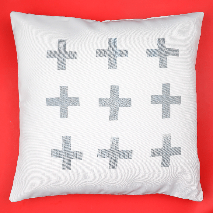 Grey and white Infusible ink throw pillow on a red background