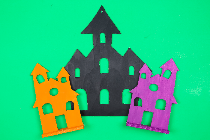 black, orange, and purple halloween houses on a green background