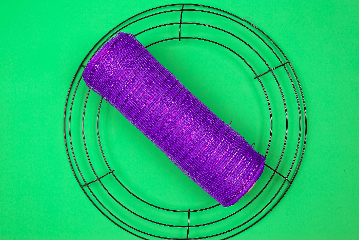 wire wreath form and purple deco mesh on a green background