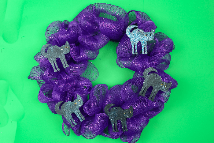 Halloween purple mesh wreath with cat shapes on a green background