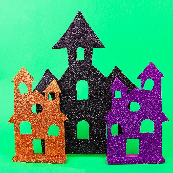 orange, black and purple glitter Halloween houses on a green background