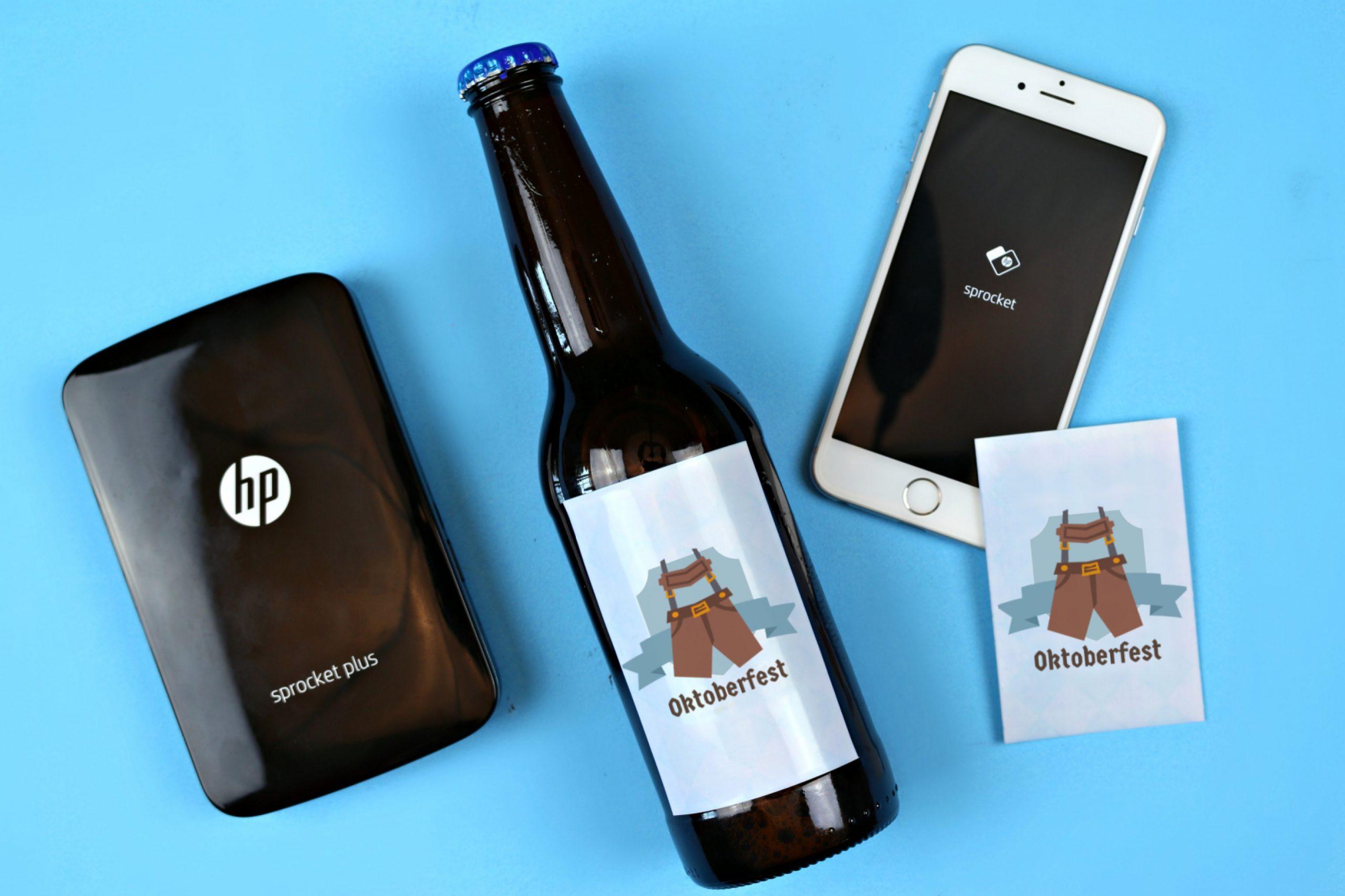 HP Sprocket, smartphone, Oktoberfest sticker and a beer bottle on a blue background