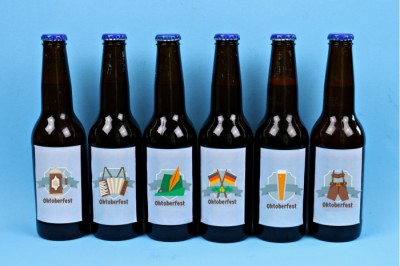 Beer bottles with printable Oktoberfest sticker labels on a blue background