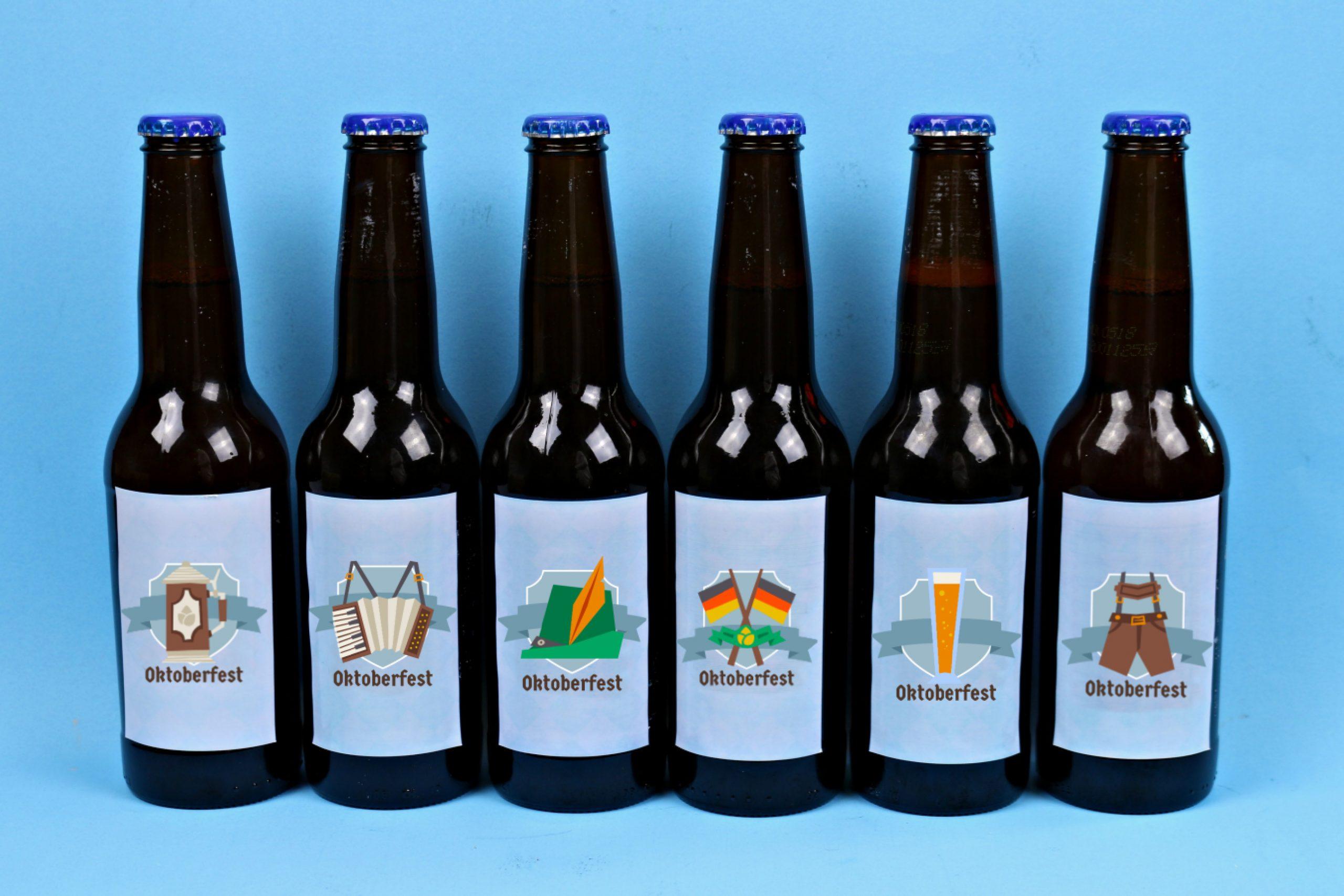 Beer bottles with printable Oktoberfest sticker labels on a blue background