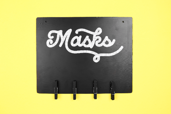 Black mask sign with hooks on a yellow background