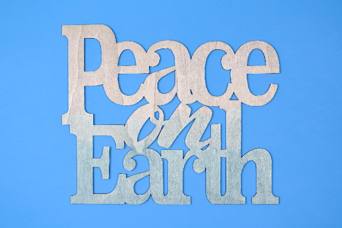 Painted wood Peace on Earth sign on a blue background