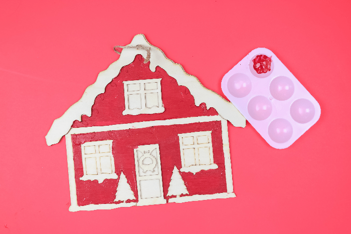 Painted Christmas house sign with paintbrush on a red background