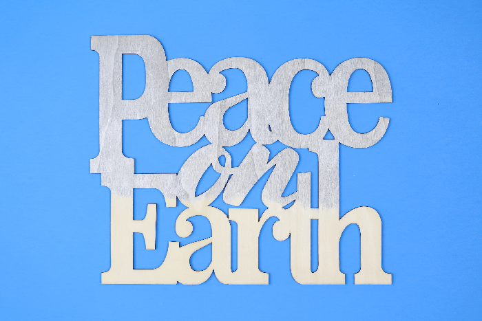 partially painted Peace on Earth sign on a blue background