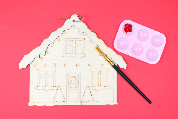 unpainted Christmas house sign with paintbrush on a red background