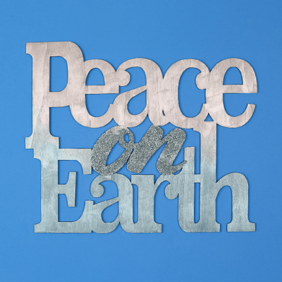 Painted and glittered Peace on Earth sign on a blue background