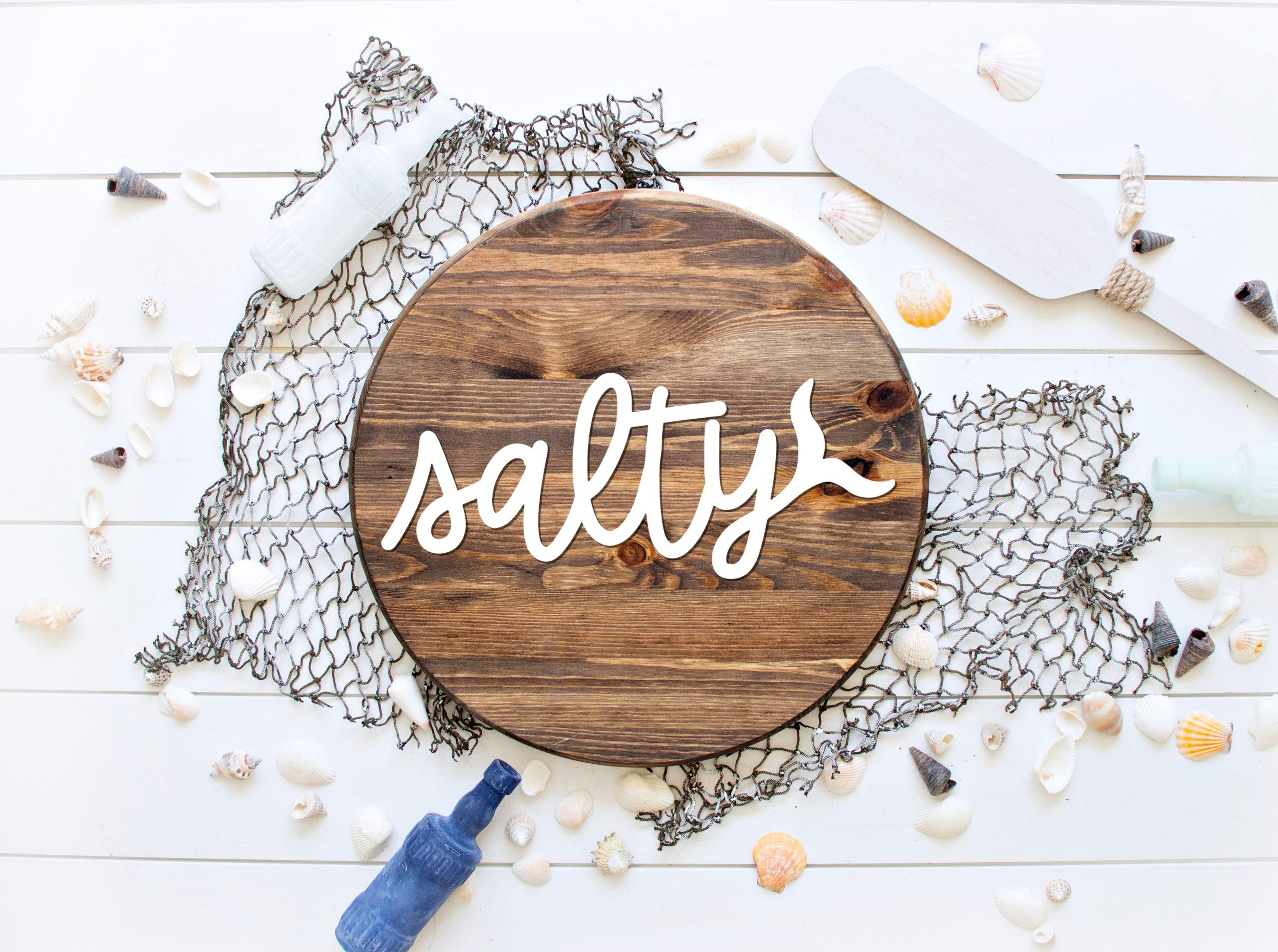 Salty SVG on a wood circle sign with beach decorations