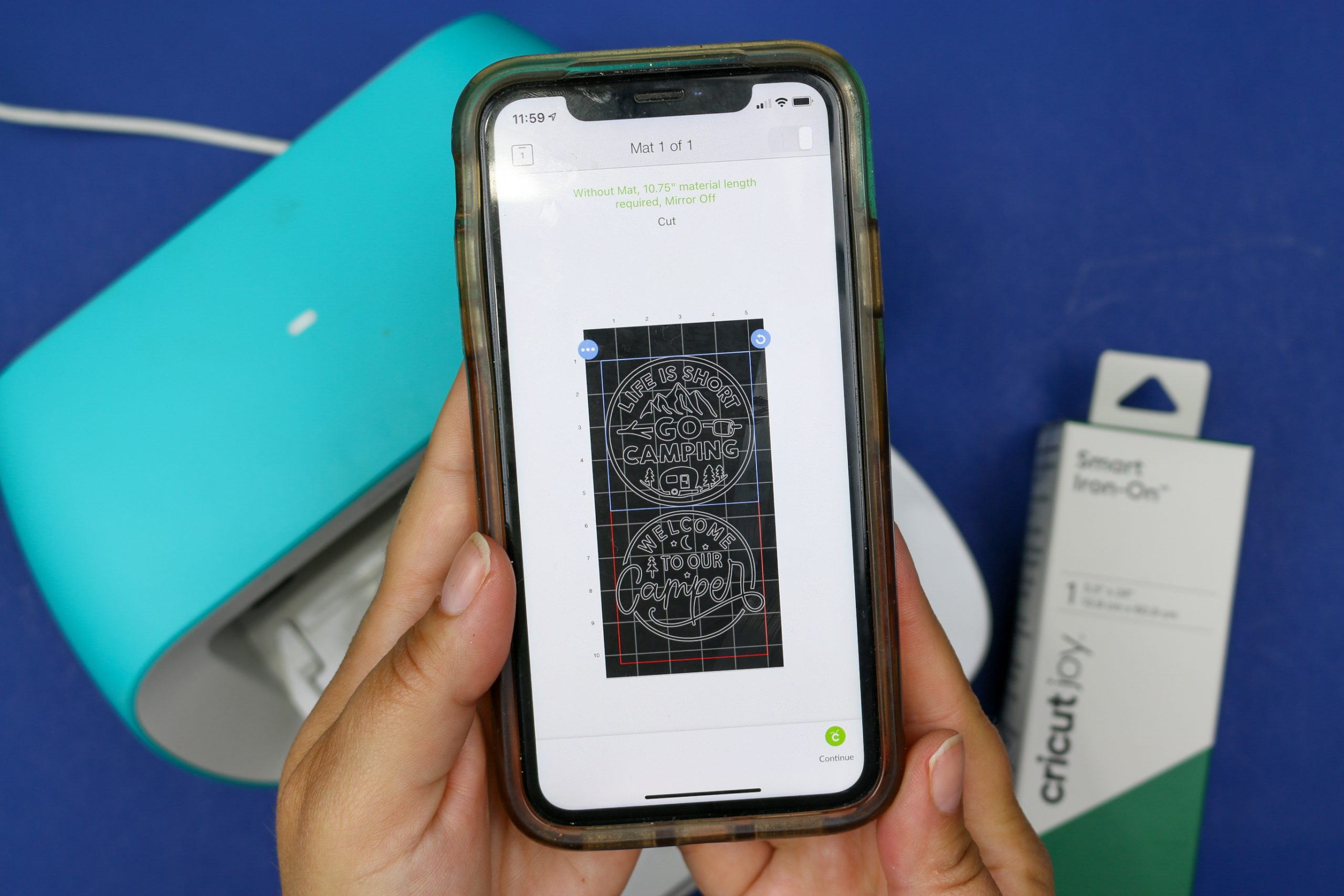 hands holding a smart phone displaying camping designs in Cricut Design Space