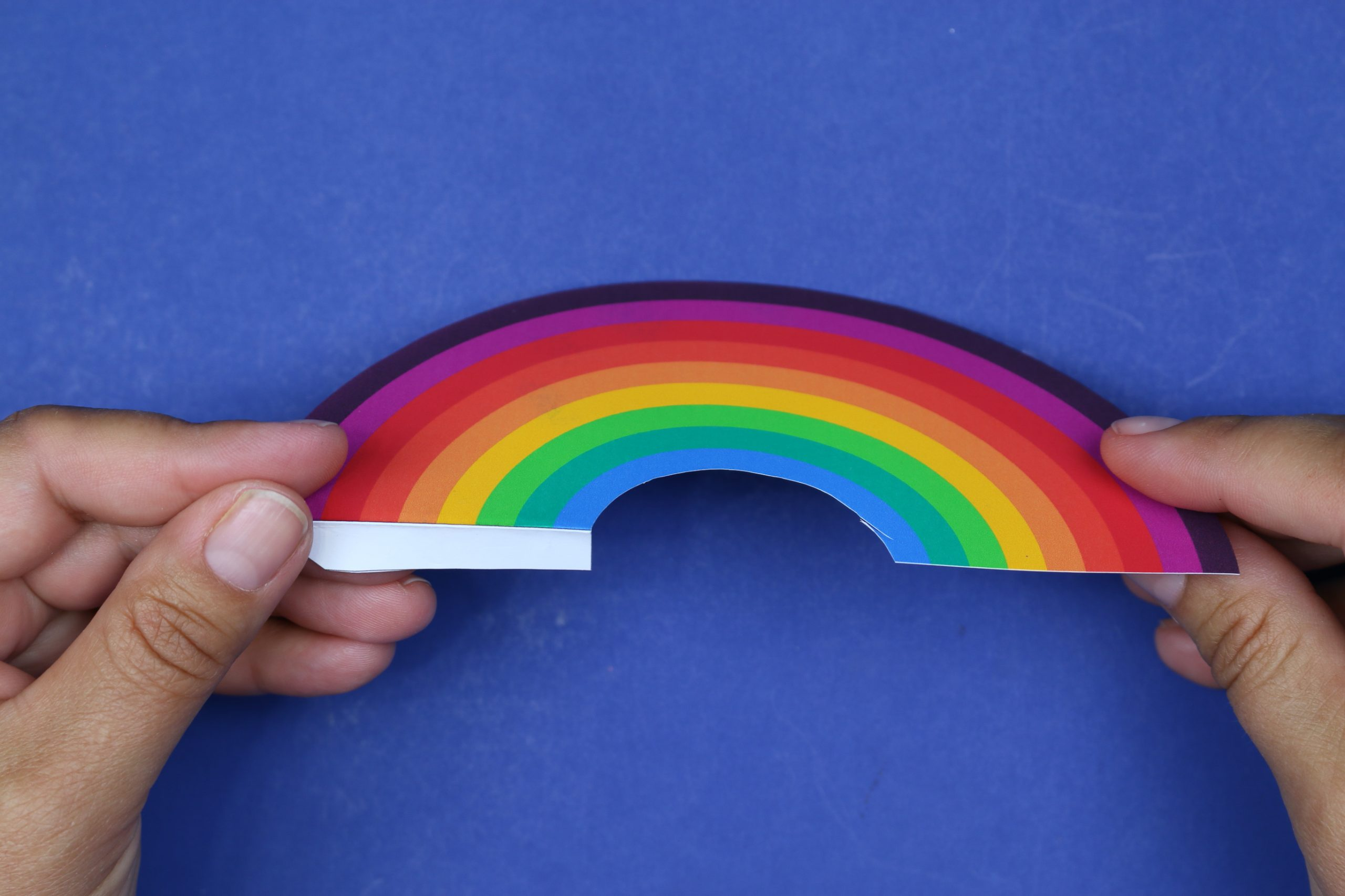hand holding a rainbow bookmark cut out from paper