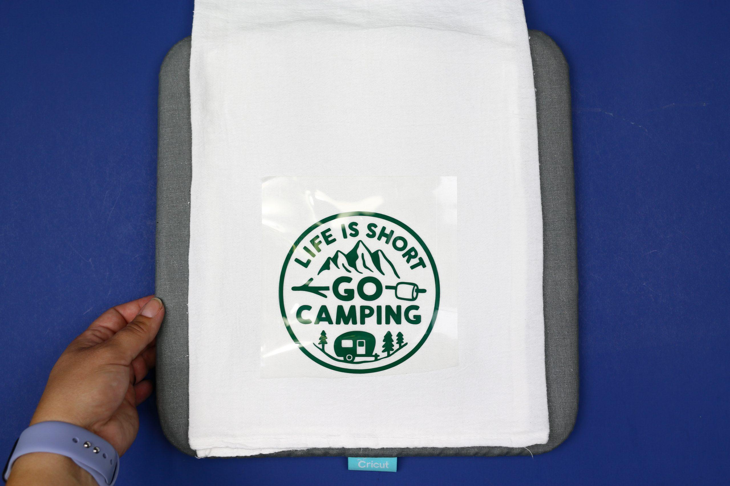 tea towel on an EasyPress mat with a green camping design