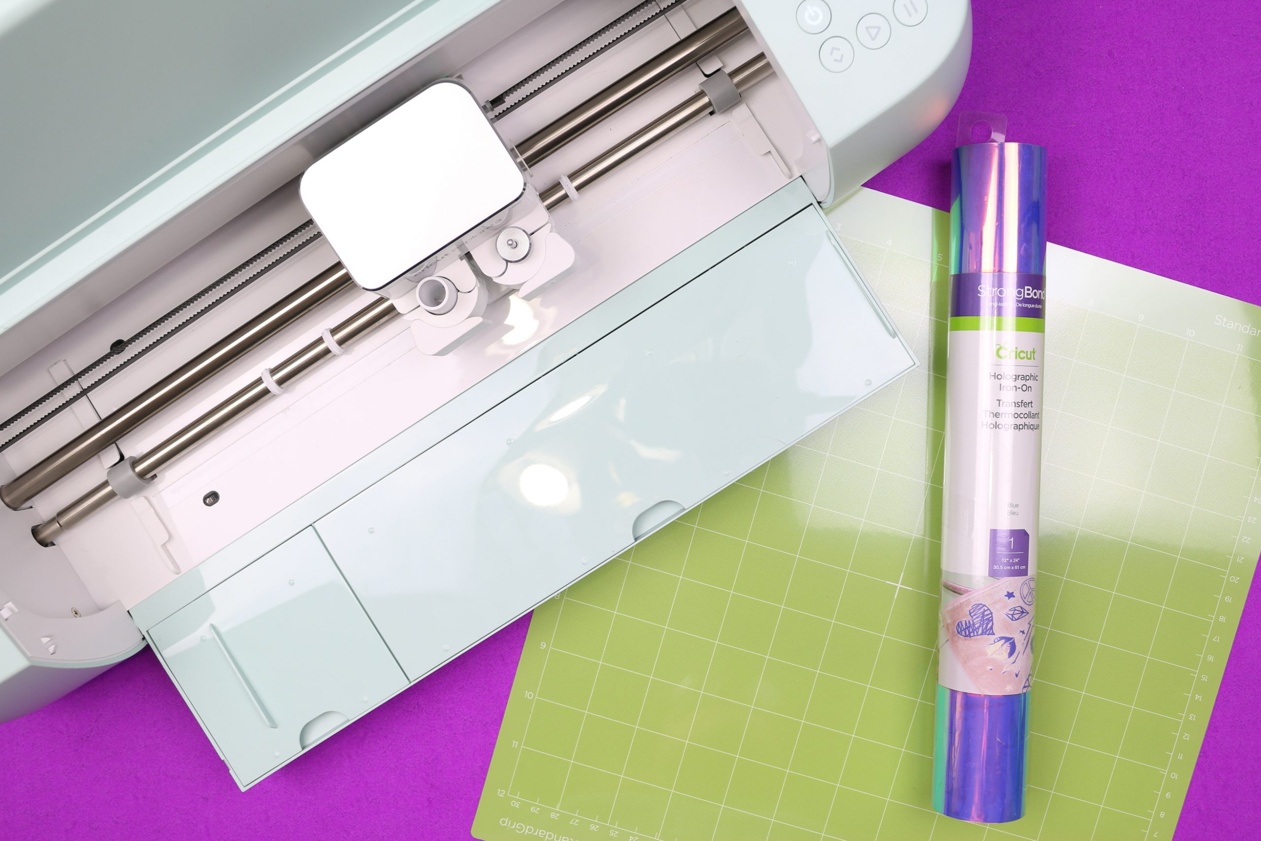 holographic iron on vinyl, a Cricut Explore 3, and a cutting mat
