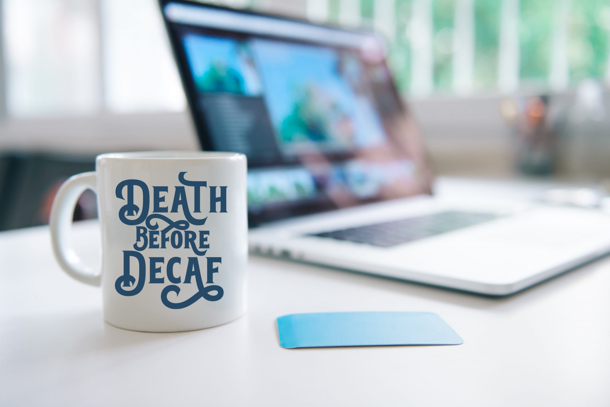 white mug that reads Death Before Decaf on a desk next to a laptop