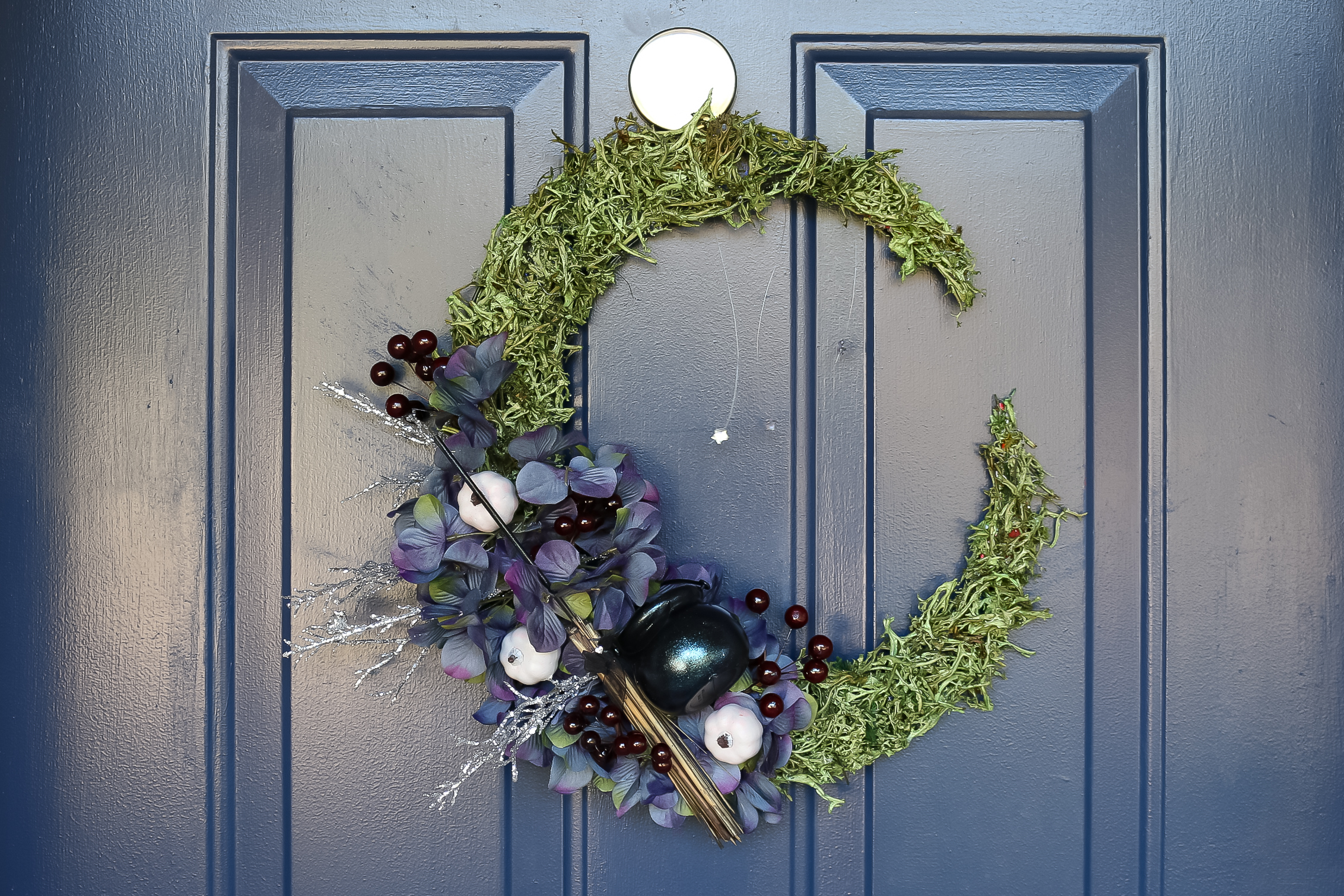 floral crescent moon wreath on a blue door