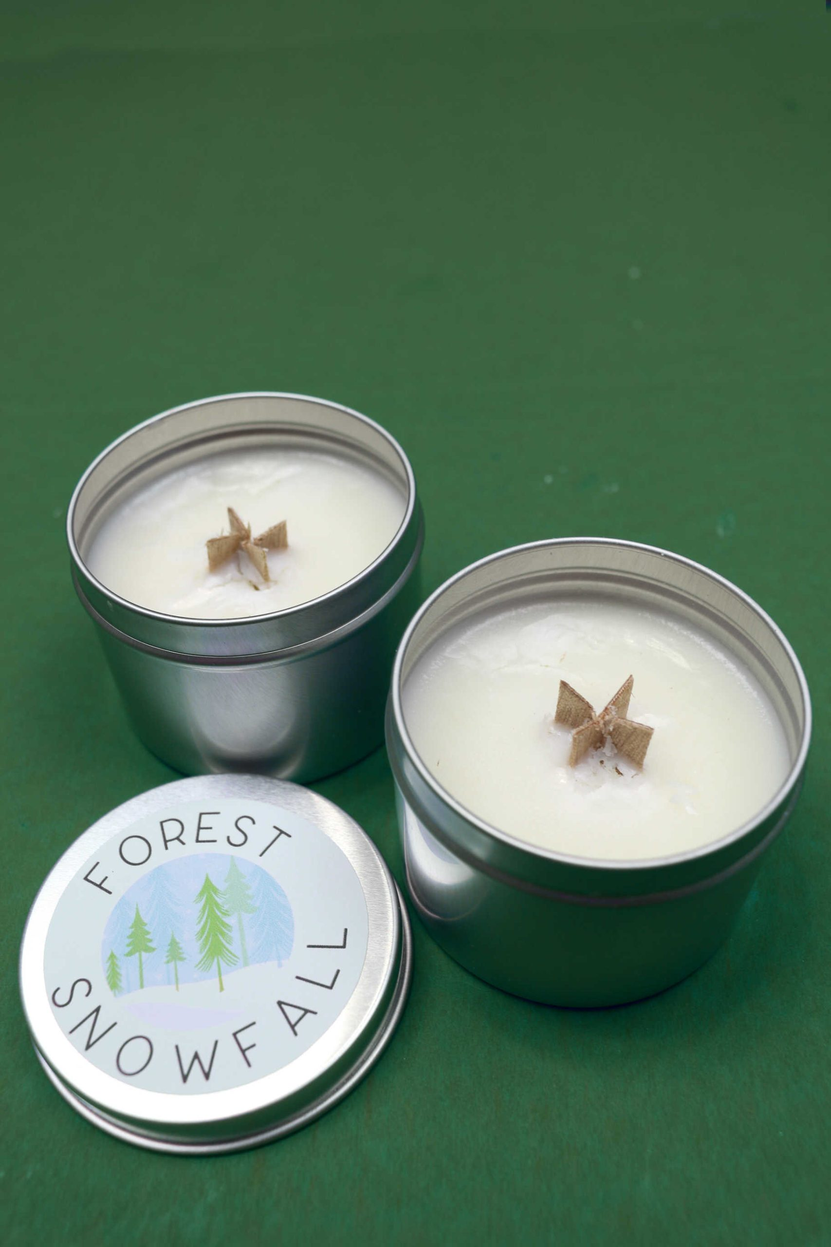 two wood wick candles in tins